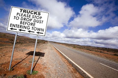 Outback Road Sign. Road sign in the Australian outback, asking trucks to stop to drop dust before entering town.  Outside Broken Hill, in western New South Wales Stock Photos