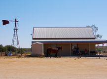 Outback Scene. At Silverton, a horse it outside a broken store where people sit in the shade to escape the blistering heat, near a ruined windmill (Australia Royalty Free Stock Images