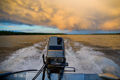 Outboard in Motion. A boat flies through the water near sunset stock photography