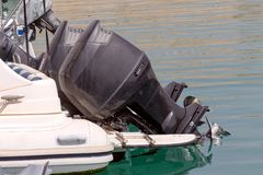 The outboard motor. The black, used, outboard motor on a moored boat close-up Stock Photography
