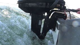 Outboard Motor 2. Profile view of outboard motor on boat with wake running with jet of water cooling the motor stock footage