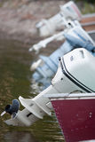 Outboard motors. A line up of outboard motors on a lake Stock Image