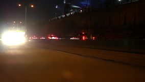 Outbound moving highway traffic at night as scene from near a guard rail.  stock footage