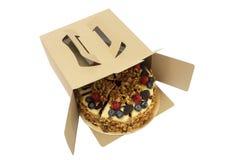 Outboxing av kakan med blåbäret och hallonet på leksaken Royaltyfri Foto
