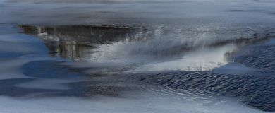 Abstract reflections in icy pond Iceland. Abstract swirls and reflections in icy stretch of frozen water in Iceland in winter royalty free stock photo