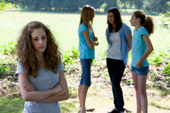 Outcast. Sad young teenage girl standing with folded arms as her teenage peers ignore her and stand in a group chatting , conceptual of a social outcast Stock Photo
