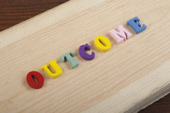 OUTCOME word on wooden background composed from colorful abc alphabet block wooden letters, copy space for ad text. Word on wooden background composed from Stock Images