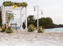 用在热带沙子海滩, outd的花装饰的婚礼曲拱 免版税库存照片