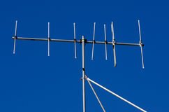 Outdated analogue tv antenna. An Outdated analogue tv antenna against blue sky stock photography