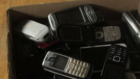 Outdated cell phones are in a big pile in a cardboard box.