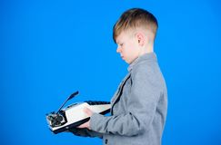 Outdated gadget. Retro and vintage. Yard sale. Retrospective study. Boy hold retro typewriter on blue background. What. To do with this thing. Out of date. I stock photo