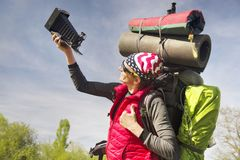 Huge novice backpack in the mountains. An outdated way of traveling is a huge uncomfortable backpack stuffed with cumbersome heavy equipment. Ancient camera- as Royalty Free Stock Images