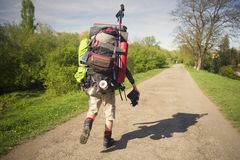 Huge novice backpack in the mountains. An outdated way of traveling is a huge uncomfortable backpack stuffed with cumbersome heavy equipment. Ancient camera- as Stock Photo
