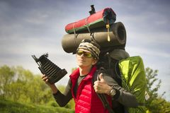 Huge novice backpack in the mountains. An outdated way of traveling is a huge uncomfortable backpack stuffed with cumbersome heavy equipment. Ancient camera- as Stock Image