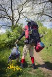 Huge novice backpack in the mountains. An outdated way of traveling is a huge uncomfortable backpack stuffed with cumbersome heavy equipment. Now things in the Stock Image