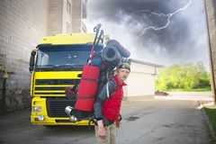Huge novice backpack in the mountains. An outdated way of traveling is a huge uncomfortable backpack stuffed with cumbersome heavy equipment. Now things in the Stock Photography