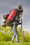 Huge novice backpack in the mountains. An outdated way of traveling is a huge uncomfortable backpack stuffed with cumbersome heavy equipment. Now things in the Royalty Free Stock Photos