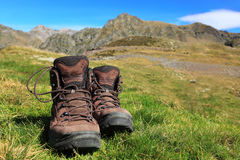Outdoor abstract. Image of a pair of hiking boots lying in the grass in front of a beautiful mountainous landscape in Pyrenees Mountains Stock Photos