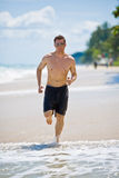 Outdoor activities. Caucasian man running on the beach with sunglasses Royalty Free Stock Images