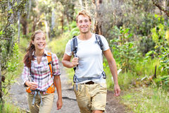 Outdoor activity couple hiking - happy hikers. Walking in forest. Hiker couple laughing and smiling. Multiracial group, Caucasian men and Asian women on Big Stock Photo