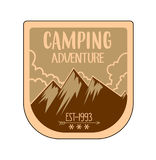 Outdoor adventure badge and retro emblem. In orange and brown oldish colours. Have mountains and clouds on background stock illustration