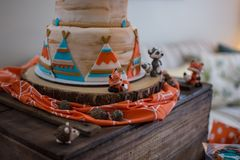 Outdoor and adventure theme cake with teepees and animal figures. Royalty Free Stock Image