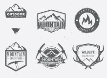 Outdoor adventures icons. Wildlife badges, mountain exploration labels in vintage style. Deer antlers, mountains, ice-axes, campfire Royalty Free Stock Photography