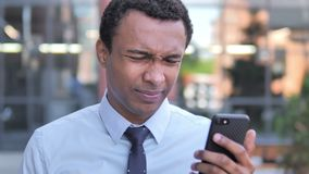 Outdoor african businessman upset by loss while using smartphone stock footage