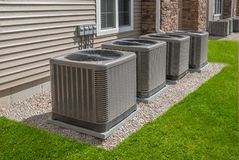 Outdoor air conditioning and heat pump units. Modern air conditioning and heating units or heat pumps, used in homes and apartments without central air stock photo