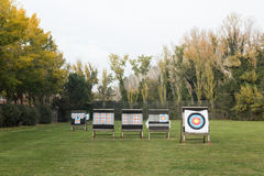 Outdoor archery targets on grass field surrounded by forest. Royalty Free Stock Images