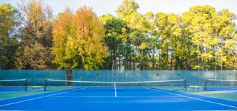 Outdoor Asphalt Tennis Courts Background. Tennis courts outside in nature with fall colorful trees in the background Royalty Free Stock Photo