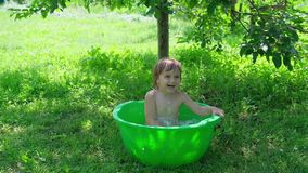 Smiling baby taking a bath and splashing in small bathtub outdoor. Outdoor baby bathing. smiling baby taking a bath and splashing in small bathtub. Hapiness and stock footage