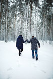 Outdoor back view portrait of cheerful man and pretty girl enjoying the snowfall in winter forest. royalty free stock photo