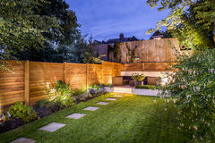 Outdoor backyard patio. Fenced backyard with patio deck and outdoor furniture illuminated in evening Stock Photos