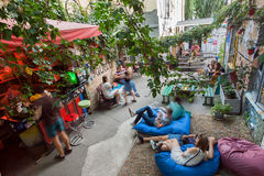 Outdoor bar with group of students relaxing under trees in rustic courtyard Stock Photos