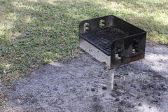 Outdoor Barbecue Grill in Ground Near Grass. One small barbecue on a pole attached to the ground outside near grass on a sunny day. Barbecue grill on a metal stock images