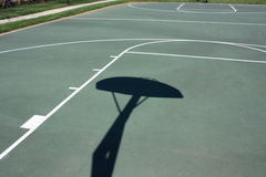 Outdoor Basketball Court. An outdoor basketball court with the shadow of the backboard and goal Royalty Free Stock Image