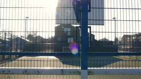 Outdoor Basketball Court Behind a Fence on a Sunny Day 2. A basketball court is filmed as the camera pans from right to left on a sunny winter day stock video