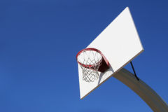 Outdoor Basketball Goal. Looking up at a street basketball goal against a clear blue sky stock images