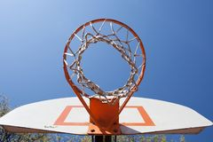 Outdoor Basketball Hoop. Basketball Hoop at an outdoor playground looking up at the sky . The sky is blue and there are trees in the background Royalty Free Stock Image