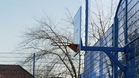 Outdoor Basketball Rim and Backboard Behind a Blue Sky. A basketball court is filmed as the camera pans from right to left on a sunny winter day stock video footage