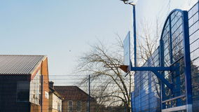 Outdoor Basketball Rim and Backboard Behind a Blue Sky. A basketball court is filmed as the camera pans from right to left on a sunny winter day stock footage