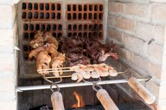 Outdoor sea food BBQ. Outdoor BBQ grill cooking shrimp, chicken and steak royalty free stock images
