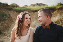Outdoor beach wedding ceremony, close up of stylish happy smiling groom and bride are having fun and laughing looking at each othe. R Royalty Free Stock Images