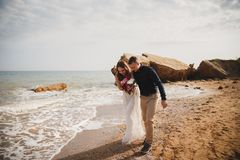 Outdoor beach wedding ceremony near the sea, stylish happy smiling groom and bride are having fun and laughing.  stock image