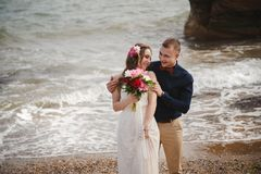 Outdoor beach wedding ceremony near the sea, stylish happy smiling groom and bride are having fun and laughing.  royalty free stock photo