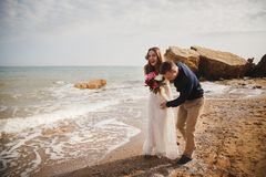 Outdoor beach wedding ceremony near the sea, stylish happy smiling groom and bride are having fun and laughing.  stock photo