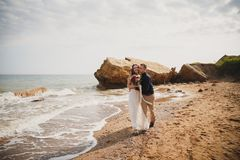 Outdoor beach wedding ceremony near the sea, stylish happy smiling groom and bride are kissing and having fun.  Stock Photo