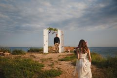 Outdoor beach wedding ceremony, stylish happy groom is standing near wedding arch on the sea shore waiting for the bride.  Stock Photo