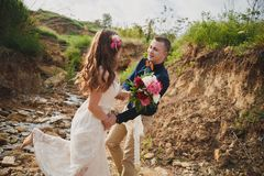 Outdoor beach wedding ceremony, stylish happy smiling groom and bride are having fun and laughing.  stock photography